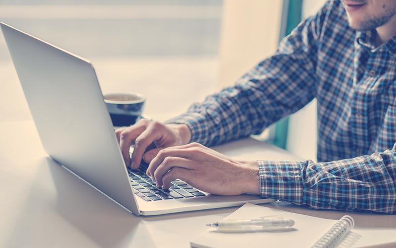 Hombre escribe en su computador portátil