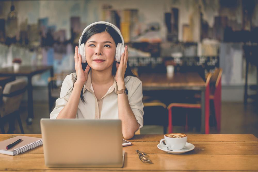 Mujer escuchando música y trabajando desde su casa
