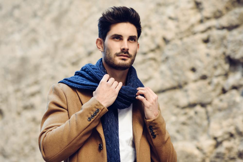 Un hombre que lleva puesta una bufanda y un blazer café.