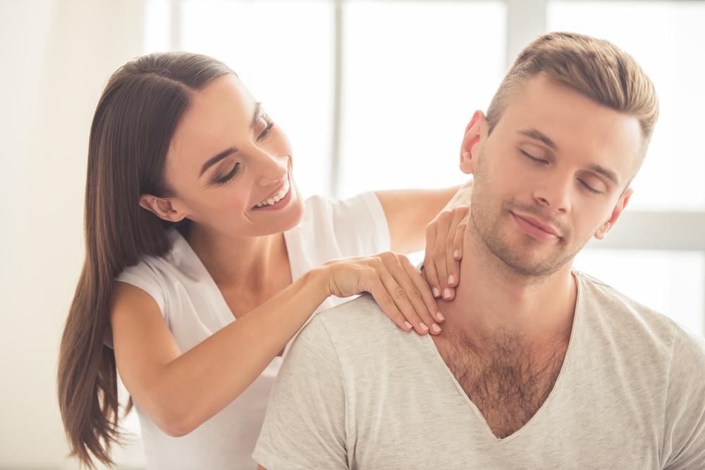 Mujer haciéndole un masaje a su pareja.
