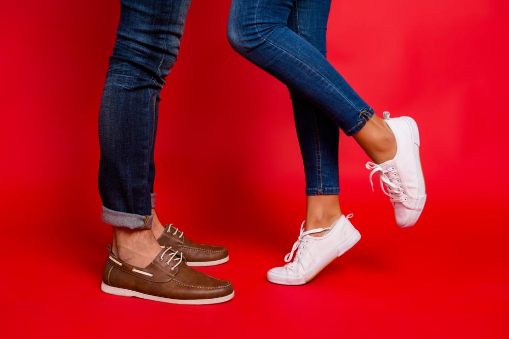Hombre con zapatos de cuero y una mujer con tenis blancos.