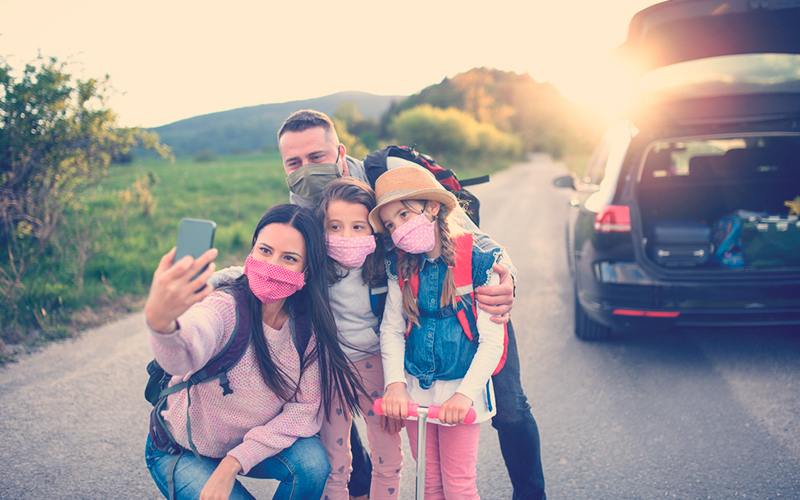 Familia colombiana con tapabocas viajando por Colombia en carro