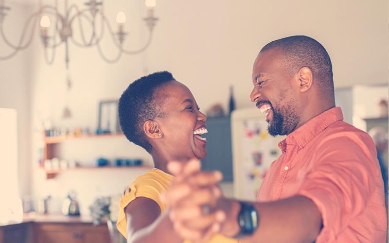 Pareja afro sonriendo mientras bailan