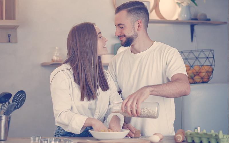 Pareja mirando cara a cara mientras cocinan juntos
