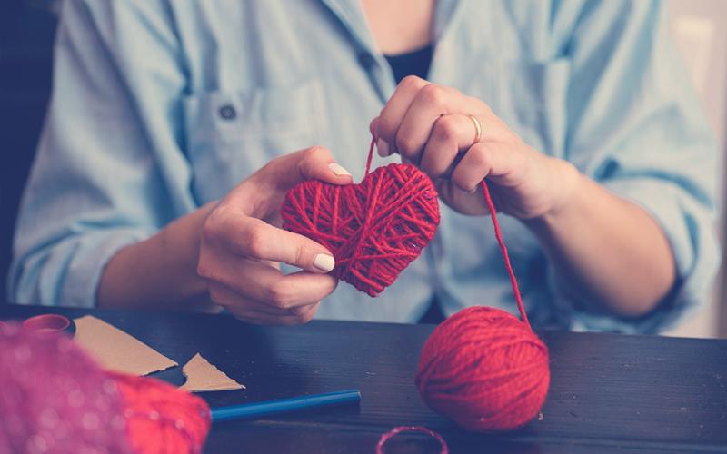 Mujer realizando una manualidad para el día del amor y la amistad o San Valentín