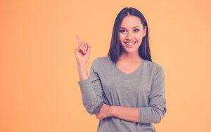 Mujer sonriendo y levantando su dedo indice
