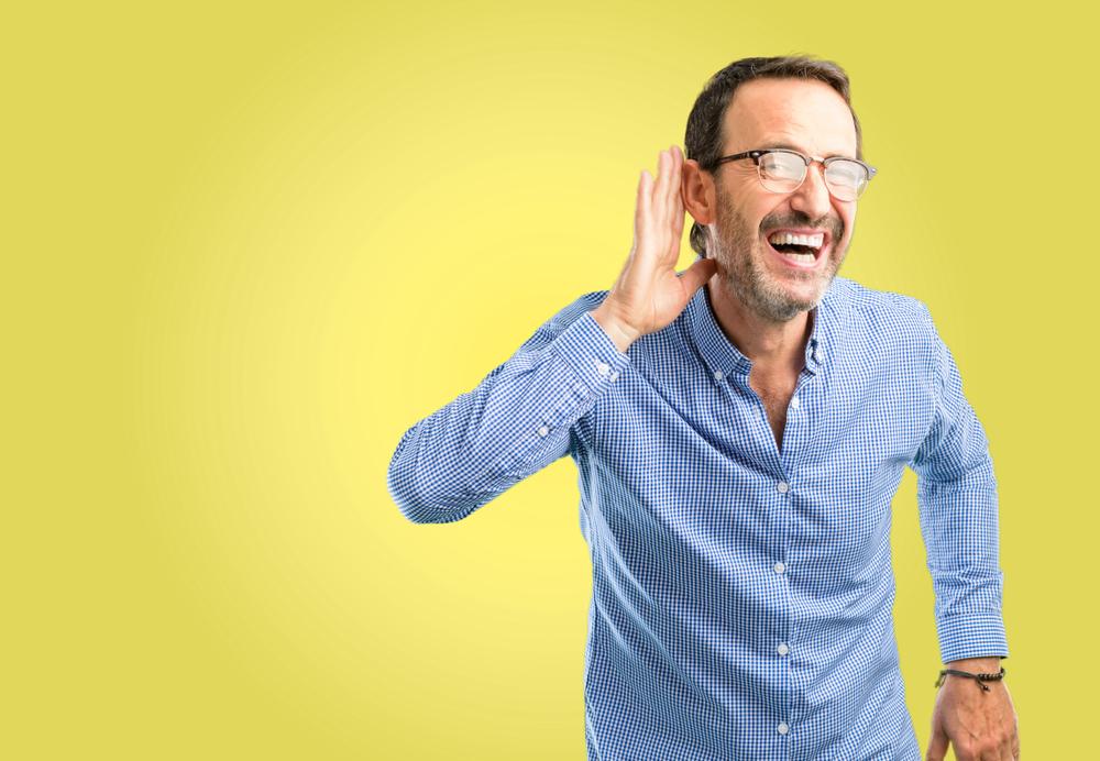 Un hombre guapo de mediana edad que está cerca del oído tratando de escuchar noticias interesantes que expresan concepto de comunicación y chismes