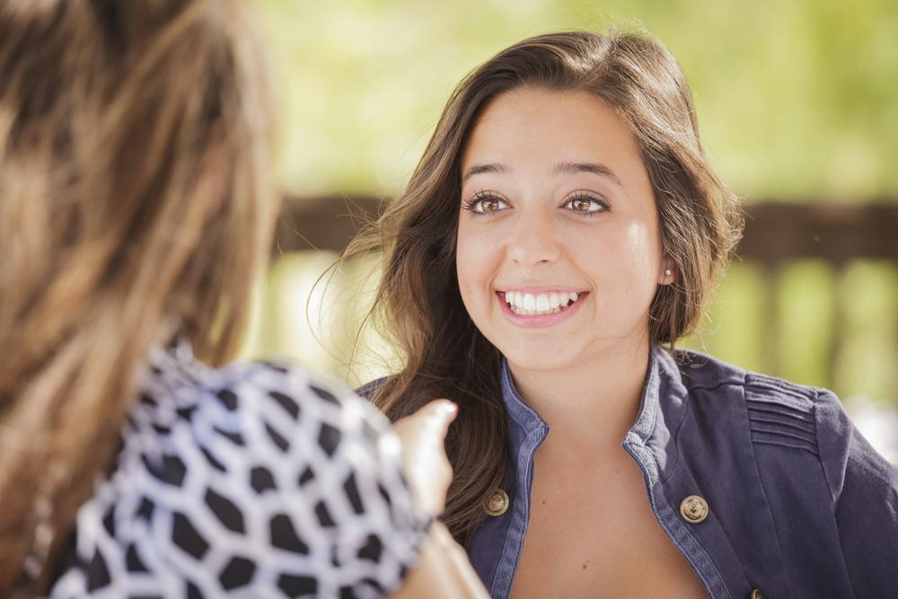 Mujer sonriente hablando con una amiga