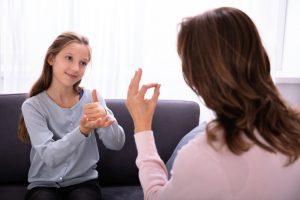 Niña utilizando la lengua de señas para comunicarse