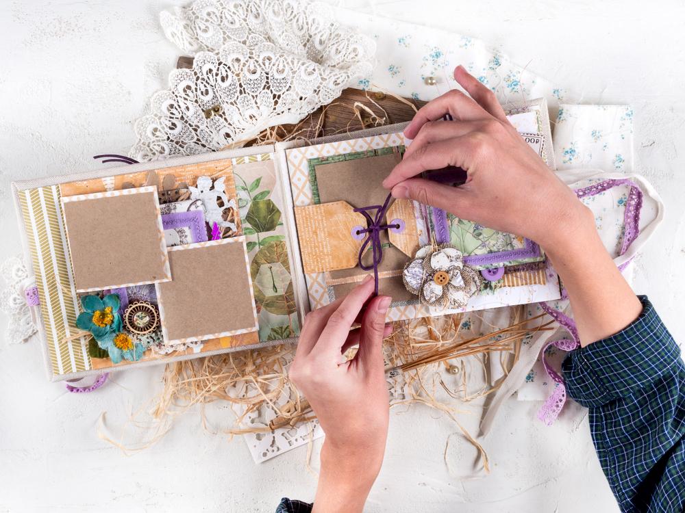 Mujer decorando un álbum de fotos hecho a mano