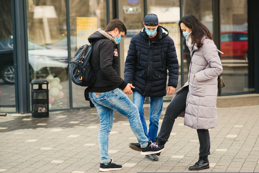 Personas saludándose con el pie mientras usan mascarillas