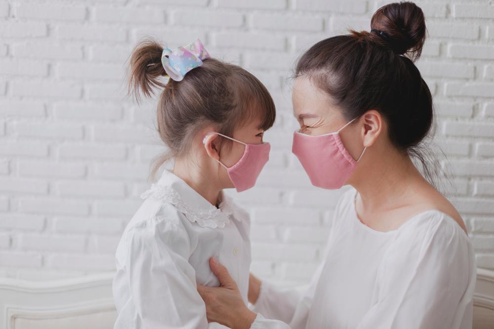 Madre e hija están contentas de usar máscara de tela hecha a mano.