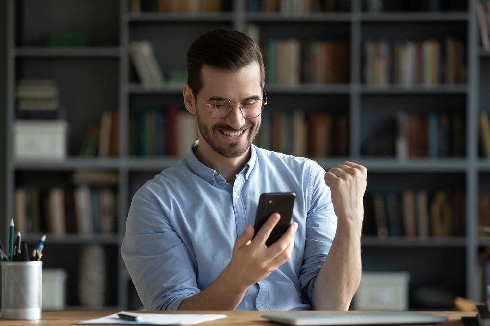 Emprendedor mirando su celular y celebrando