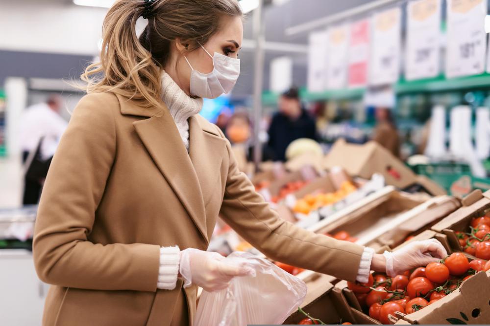 Una joven compra tomates en un supermercado. Mujer con mascarilla facial y guantes para prevenir la infección.