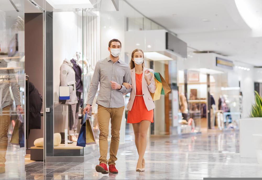 Pareja con tapabocas caminando en un centro comercial