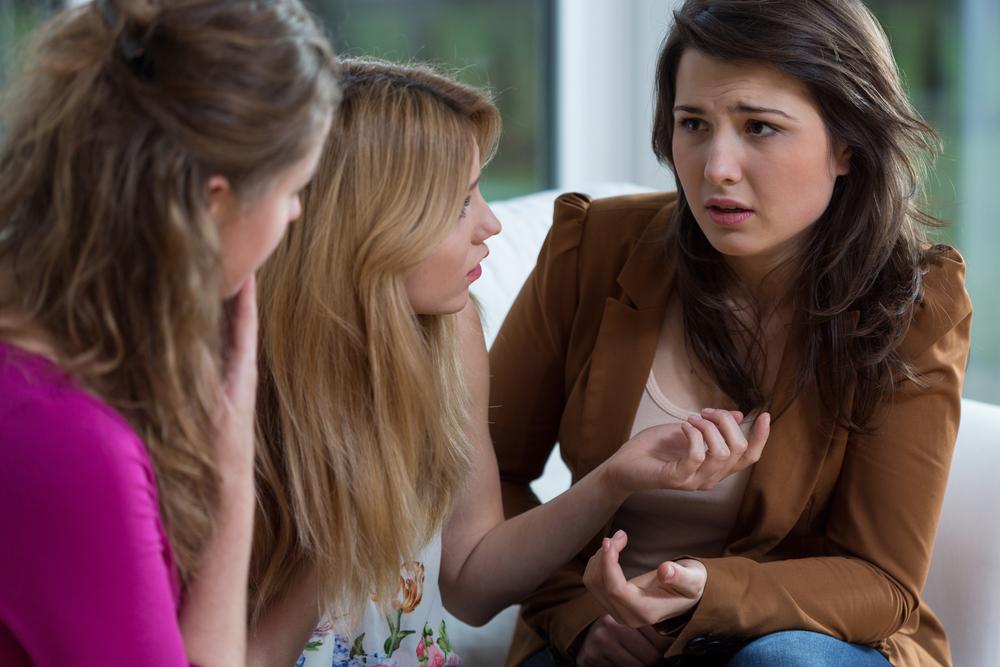 Mujer angustiada hablando con sus amigas