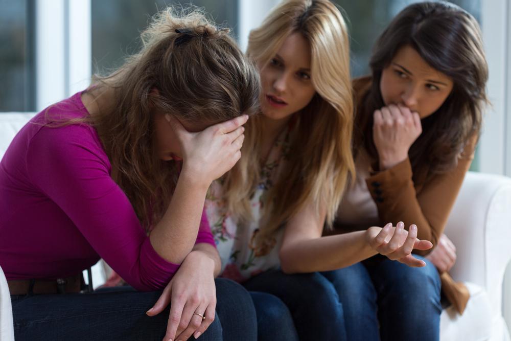 Mujer triste hablando con sus amigas