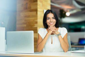 Mujer emprendedora onriendo al lado de un computador portátil