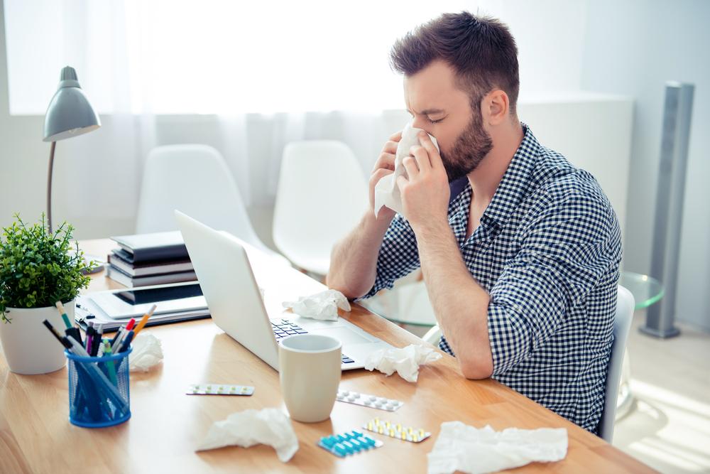 Hombre estornudando sobre un escritorio mientras trabaja en casa