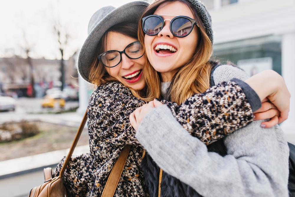 Amigas sonriendo y abrazándose