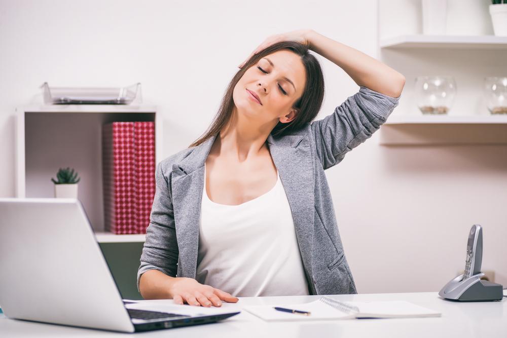 Mujer realizando pausas activas mientras trabaja