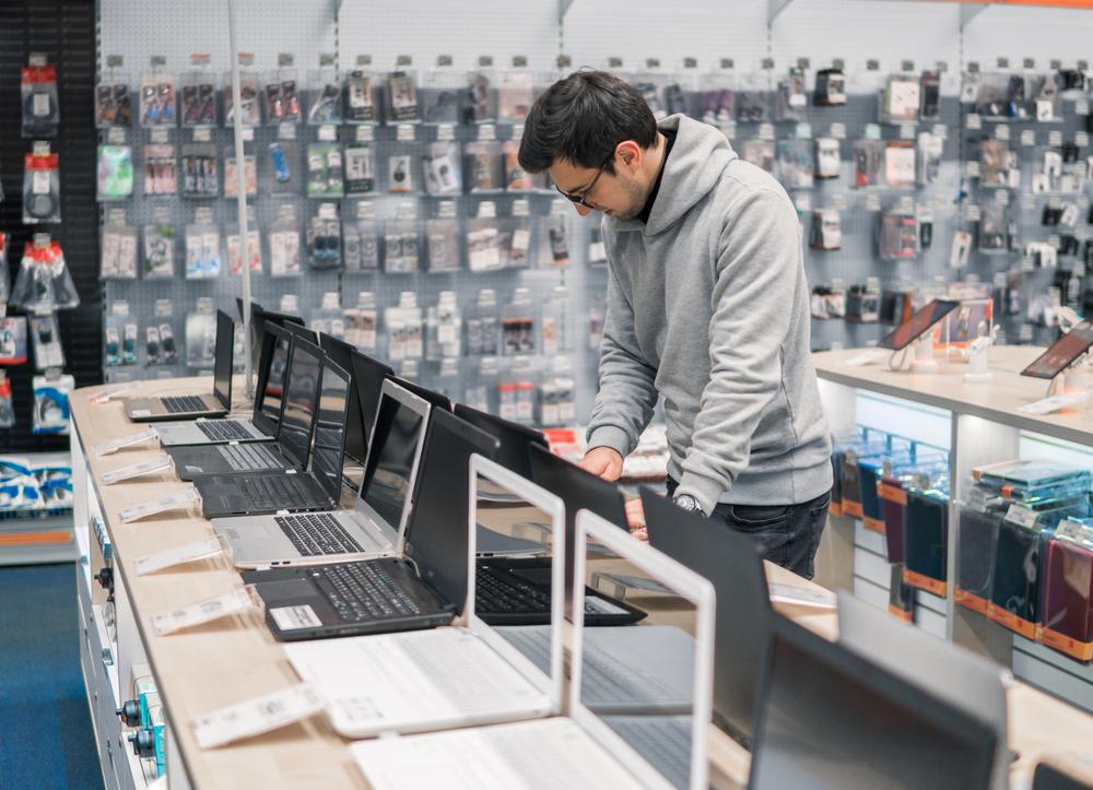 Hombre en una tienda de tecnología decidiendo qué computador comprar
