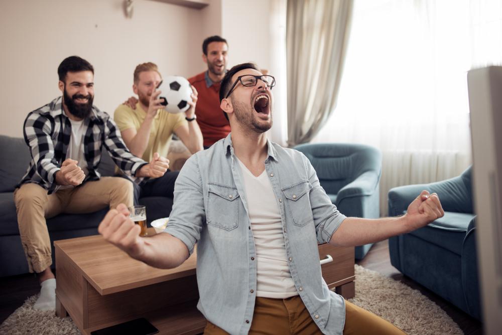 Grupo de amigos mirando un partido de fútbol