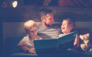Papá leyéndole a sus hijos libros de fantasía para niños