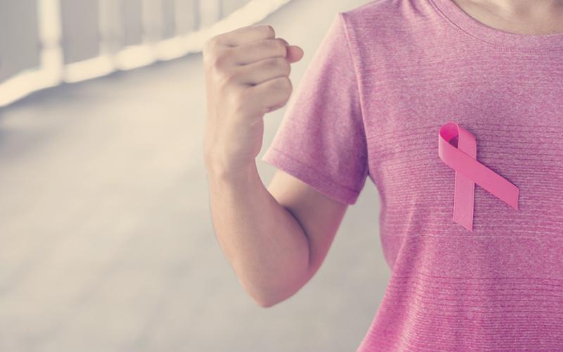 Mujer con camisa que tiene un lazo rosa representando la lucha contra el cáncer de mama