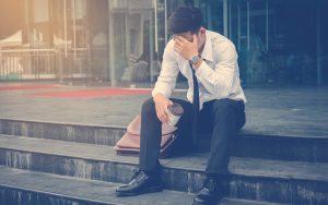 Hombre sentado y triste porque perdió su empleo