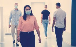 Mujer usando tapabocas y respetando las nuevas normas de etiqueta social