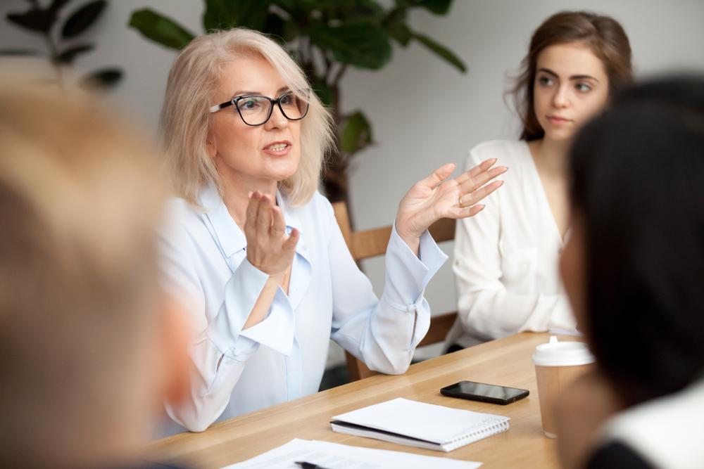 mujer líder de negocios que habla en la reunión