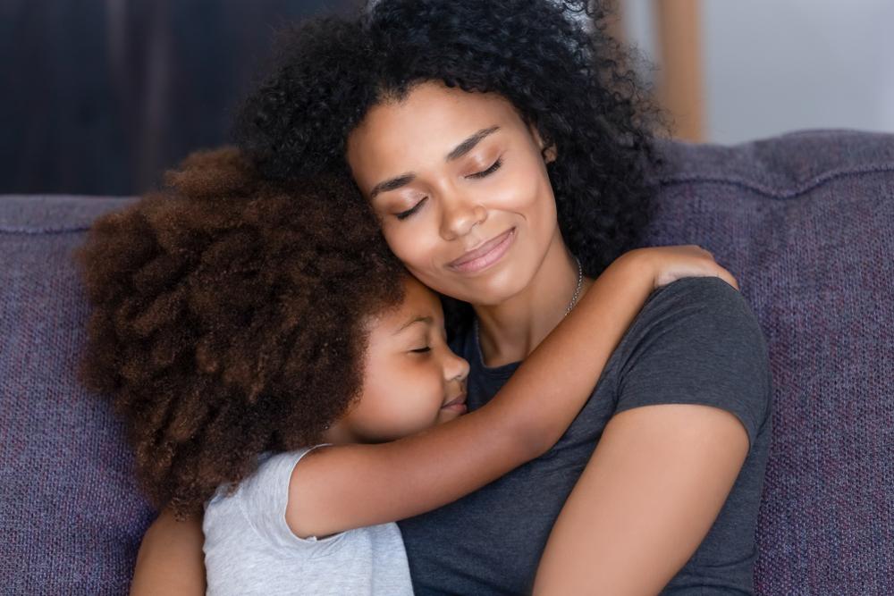 Mama e hija abrazándose sentadas en un sofá
