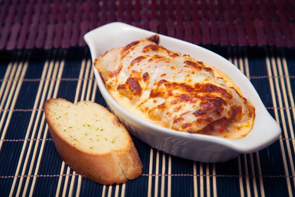 Lasaña mixta  acompañada de un pan de ajo
