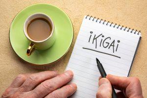 Mano de un hombre con una libreta donde escribe Ikigai
