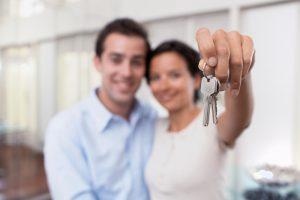 Pareja feliz con las llaves de su casa propia