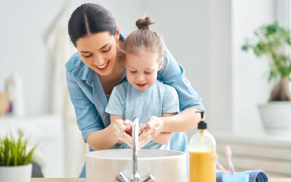 Mamá ayudándole a su hija a lavarse las manos