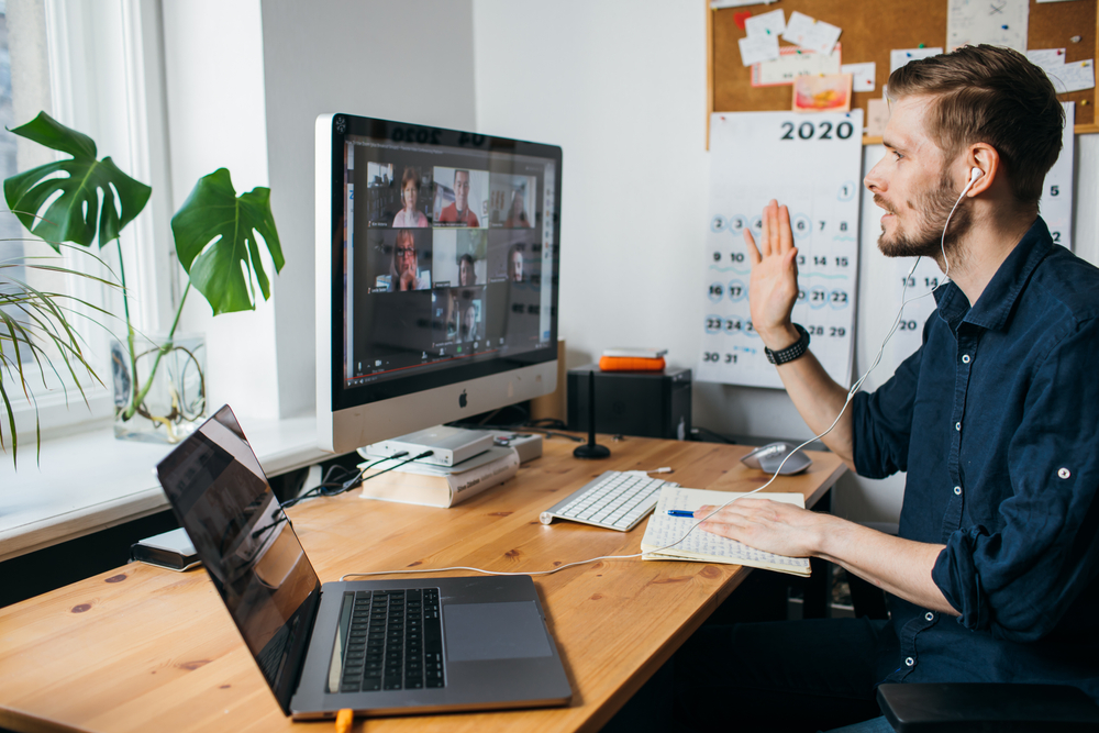 Hombre saludando en una reunión virtual