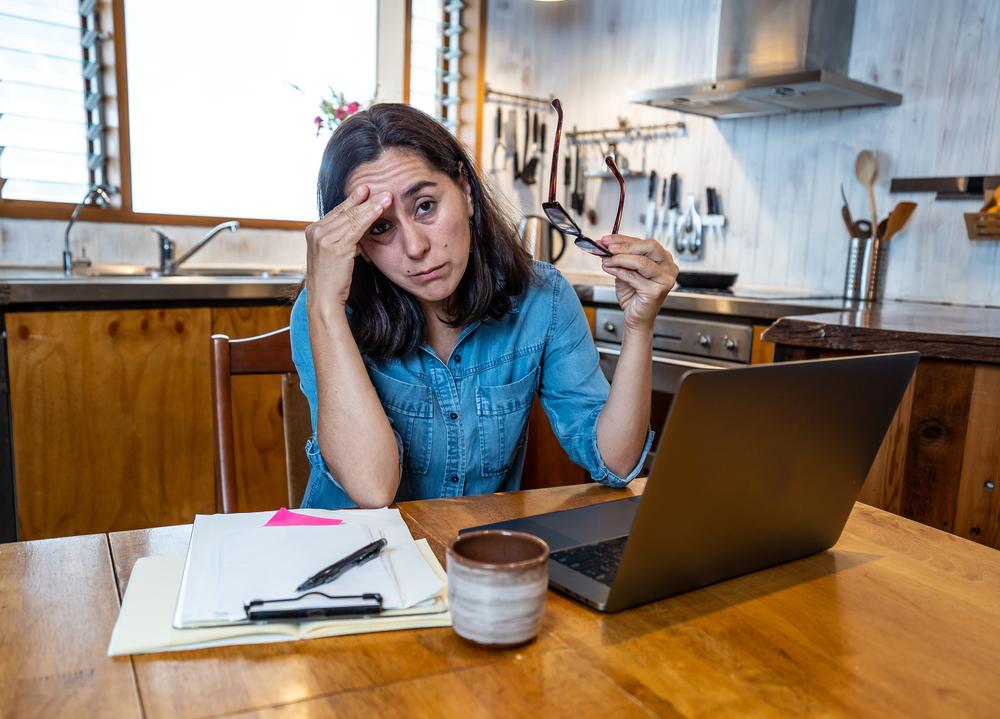 Mujer en una reunión virtual haciendo un gesto de estresada
