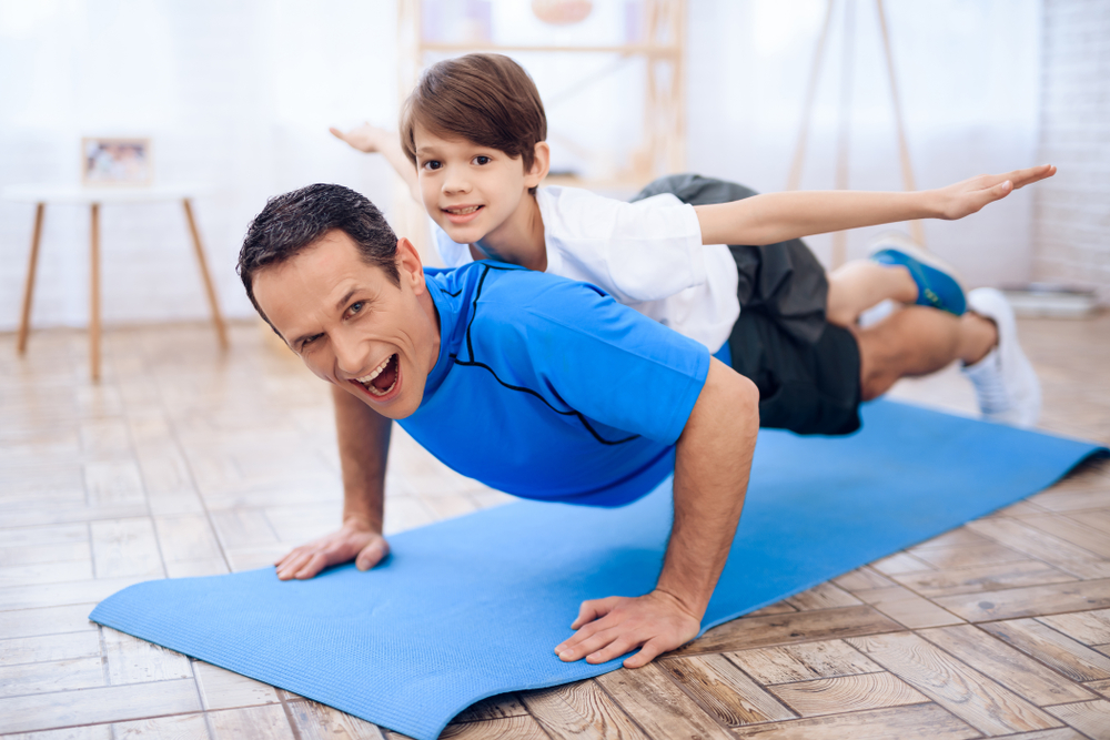 Hijo ayudándole a su papá a hacer ejercicio
