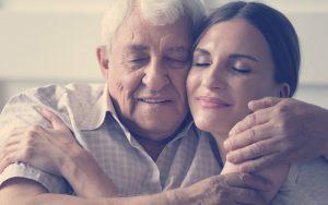 Padre e hija abrazándose mientras sonríen