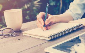 Persona escribiendo con lápiz en un cuaderno