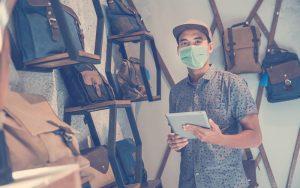 Emprendedor con una tablet usando tapabocas