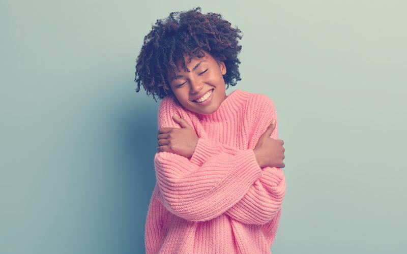 Mujer afro con un buzo rosado dándose un abrazo