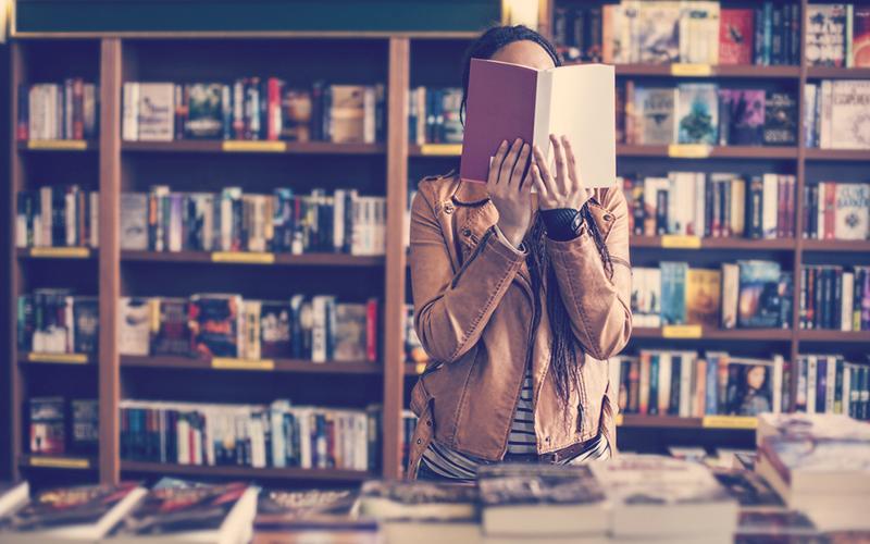 Mujer en la biblioteca leyendo un libro