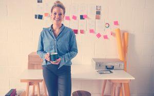 Emprendedora sonriendo con un café en la mano