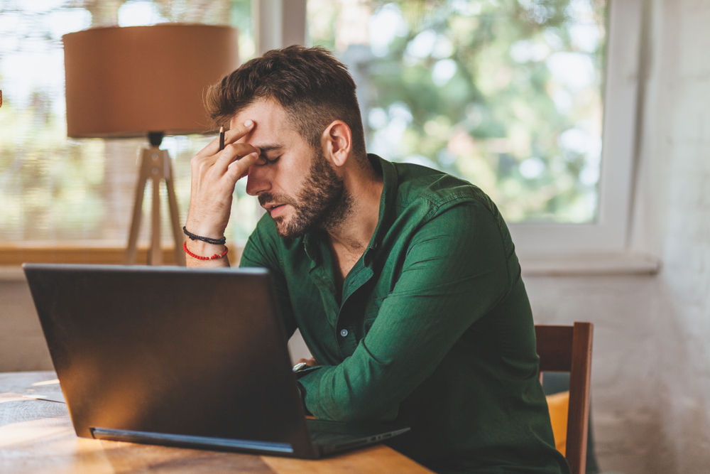 Joven con tiempo estresante trabajando en laptop