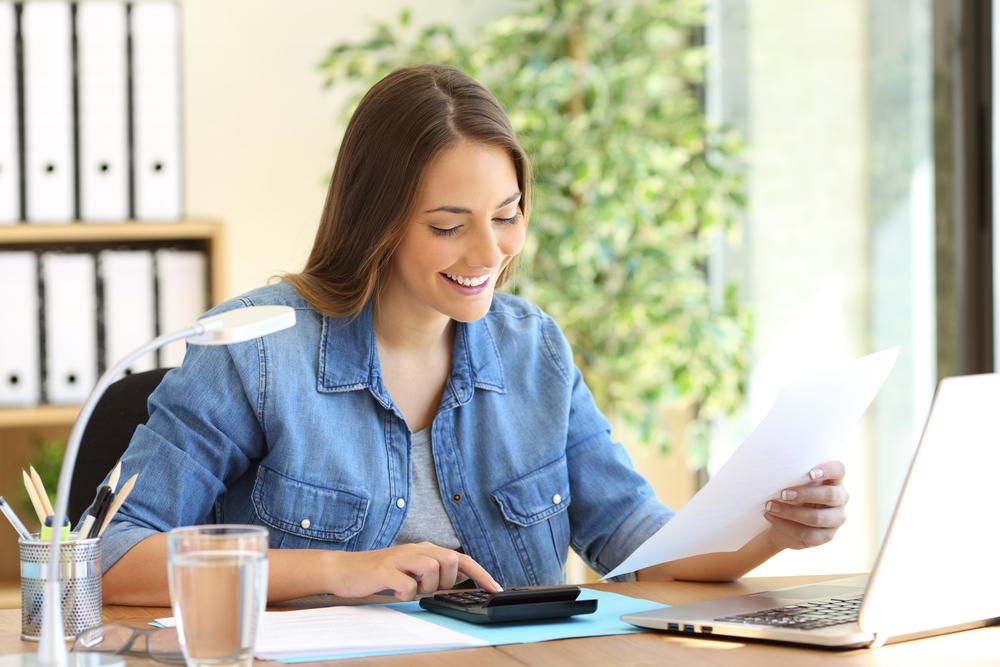 Mujer independiente calculando un presupuesto en un escritorio de la oficina
