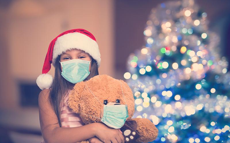 Niña con osito de peluche con máscara, coronavirus de Navidad y concepto de pandemia