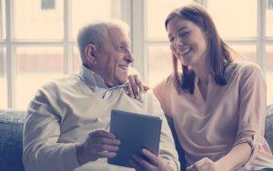 Abuelo junto a su nieta riéndose viendo una tablet